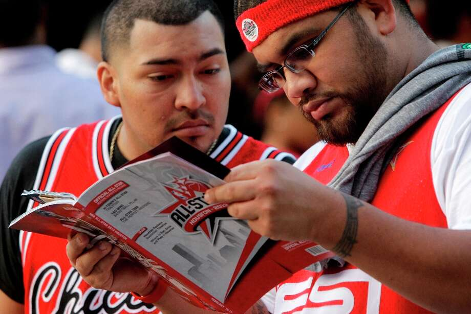 Alfonso Resendez, left, and Pedro Martinez look at a NBA All-Star program outside at the Toyota Center. Photo: Melissa Phillip, Chronicle / © 2013  Houston Chronicle
