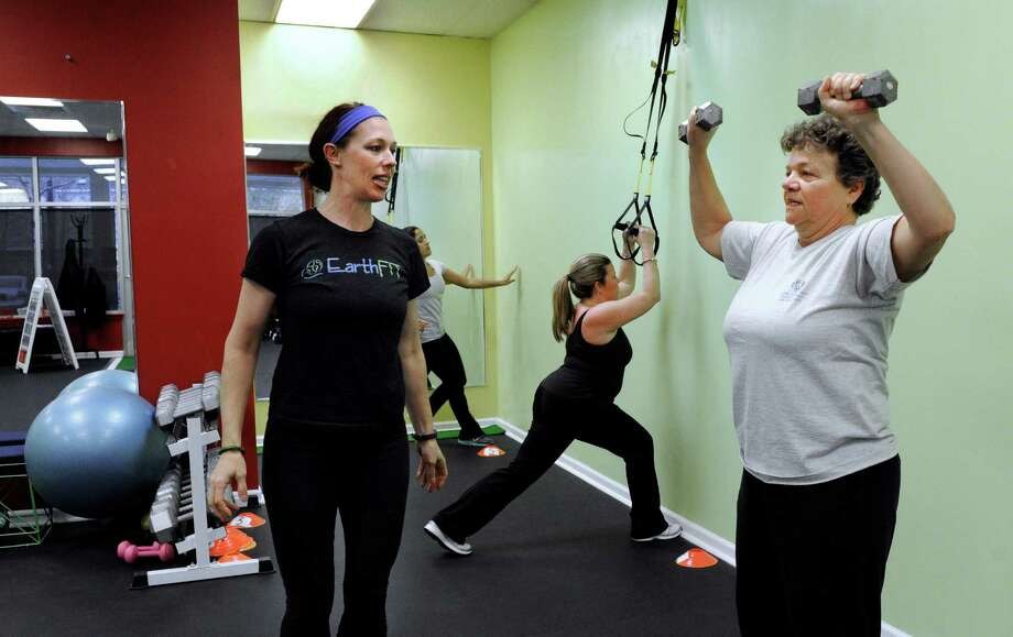 Trainer Seana Hart, owner of EarthFit, in New Fairfield, Conn., works with Joan Theriault, right, and Val Anderson, center, Thursday, Nov. 14, 2013. Photo: Carol Kaliff / The News-Times