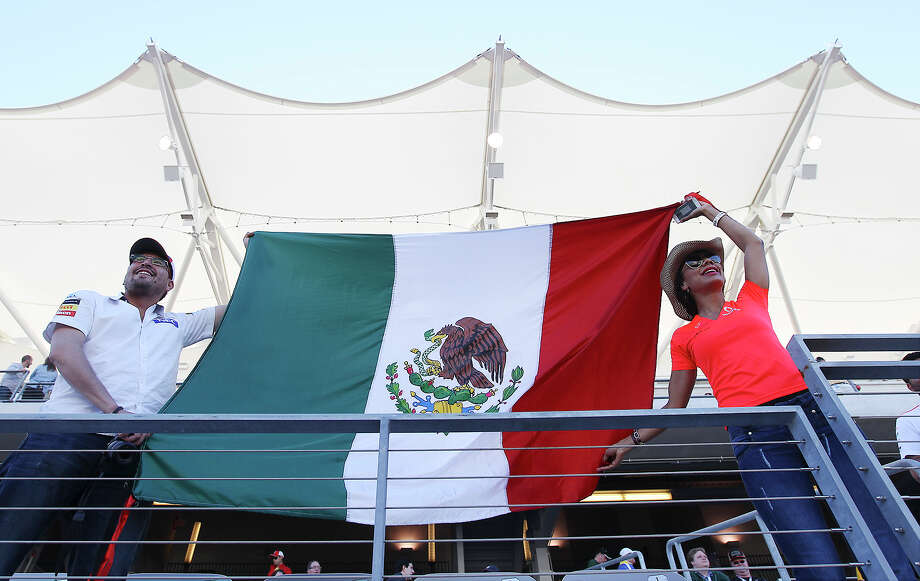 Manuel Torres (left) and Laura Luna from Puebla, Mexico show their pride for Formula One driver and fellow countryman Sergio Perez during the Formula One United States Grand Prix afternoon practice session at the Circuit of the Americas near Austin, Texas on Friday, Nov. 15, 2013. Photo: Kin Man Hui, San Antonio Express-News / ©2013 San Antonio Express-News