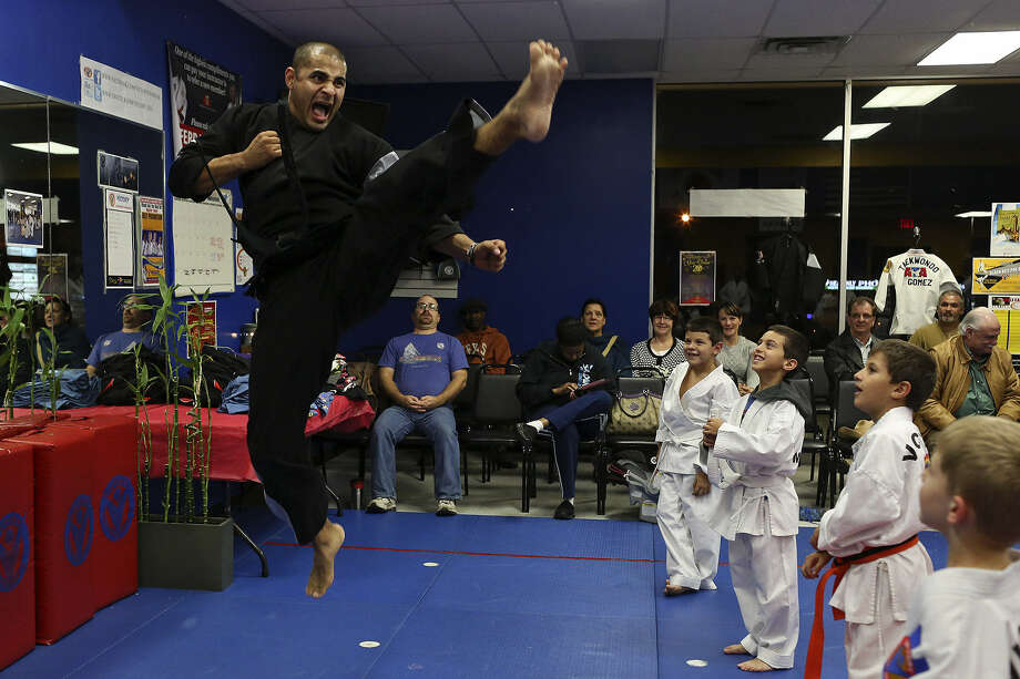 Chief instructor Raul Meza, a fourth-degree black belt, demonstrates a move for students at Victory Martial Arts as parents look on. Photo: Photos By Lisa Krantz / San Antonio Express-News
