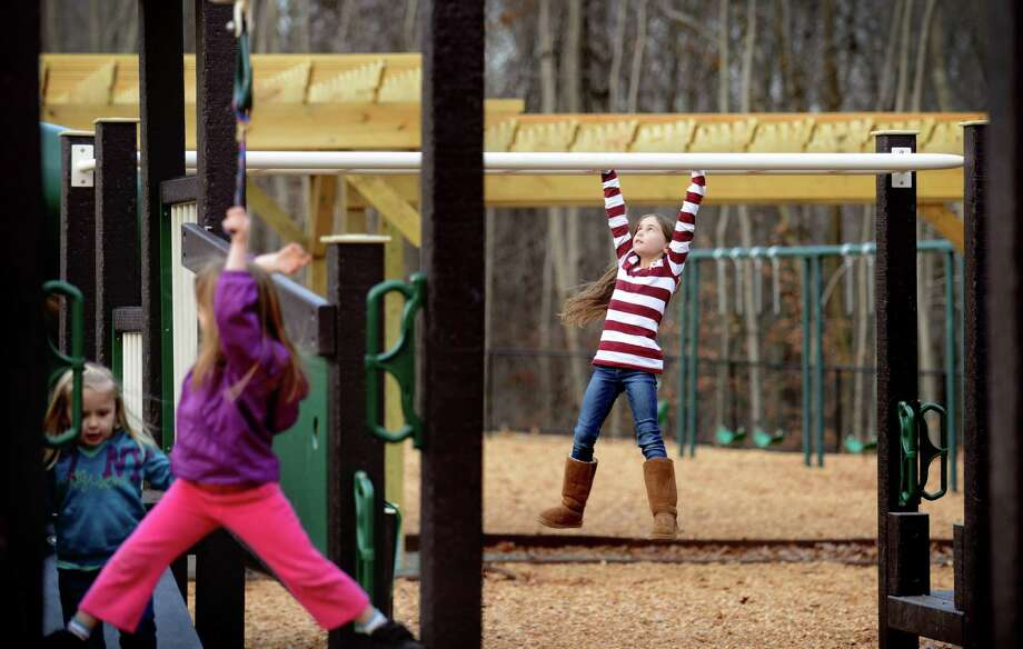 Seven-year-old Ella Caron, of Oxford, swings from the monkey bars Friday, Nov. 15, 2013 at Lily Park in Oxford, Conn.  The park on Great Oak Road completed construction last month and is dedicated to the memory of 3-year-old Lily Brooks, who died of injuries she sustained in a head-on crash Sept. 11. Photo: Autumn Driscoll / Connecticut Post