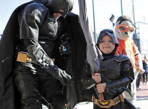 Batman and Batkid display the umbrella taken from the Penguin who kidnapped SF Giants mascot Lou Seal at AT&T Park in San Francisco Ca., on Friday Nov. 15, 2013.  Five year old Miles from Tulelake in Siskiyou County loves superheroes and Batman in particular. After battling leukemia since he was a year old Miles will fulfill his dream of becoming Batkid being swept around the city performing superhero feats from rescuing a damsel in distress to thwarting a bank robbery and even chasing down the Penguin through AT&T Park Photo: Michael Macor, The Chronicle