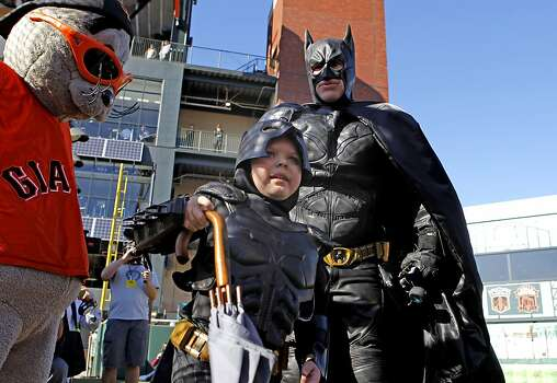 Batman and Batkid with the umbrella taken from the Penguin who kidnapped SF Giants mascot Lou Seal at AT&T Park in San Francisco Ca., on Friday Nov. 15, 2013.  Five year old Miles from Tulelake in Siskiyou County loves superheroes and Batman in particular. After battling leukemia since he was a year old Miles will fulfill his dream of becoming Batkid being swept around the city performing superhero feats from rescuing a damsel in distress to thwarting a bank robbery and even chasing down the Penguin through AT&T Park Photo: Michael Macor, The Chronicle