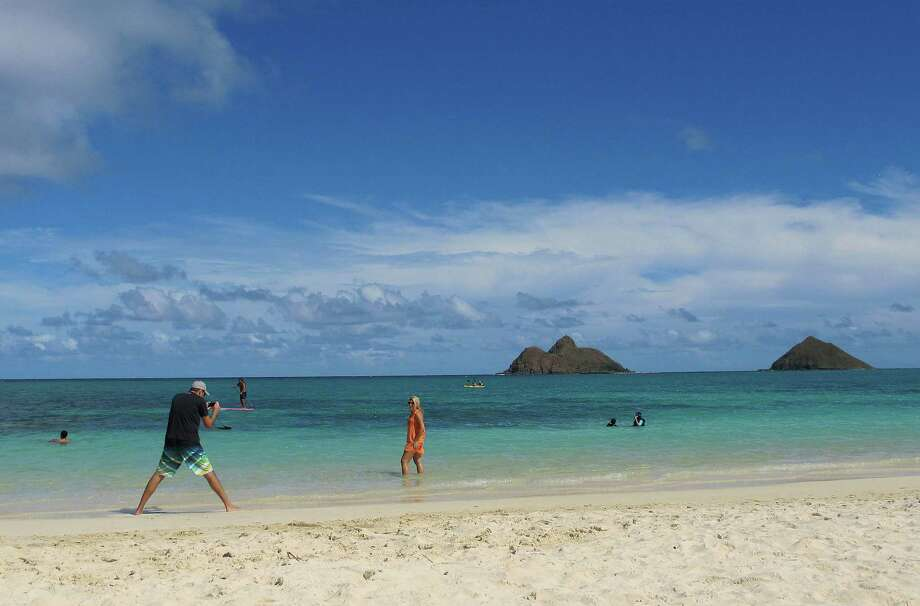 Tourists enjoy Lanikai Beach in Kailua, Hawaii. The Kailua Neighborhood Board is upset about a thriving industry of illegal bed-and-breakfast and vacation rentals and is asking the state tourism agency to stop encouraging visitors to stay overnight in their town. Photo: Audrey McAvoy, STF / AP