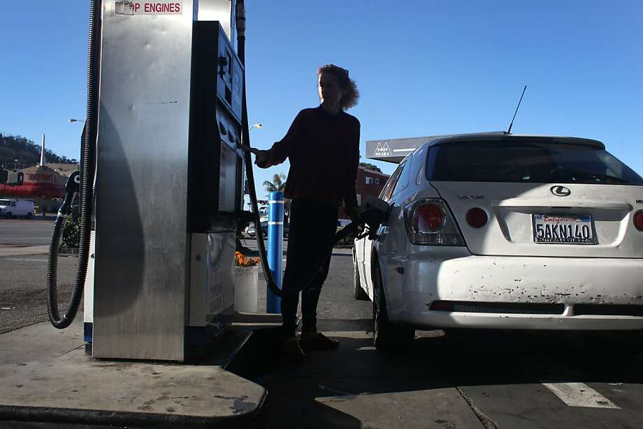 Anne Montgomery fills her car at Twin Peaks Auto Care in S.F., which offers a discount for cash, below. Photo: Pete Kiehart, The Chronicle