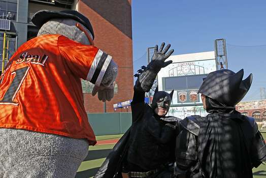 Batman and Batkid high five Lou Seal after a battle with the Penguin who kidnapped the SF Giants' mascot at AT&T Park in San Francisco Ca., on Friday Nov. 15, 2013.  Five year old Miles from Tulelake in Siskiyou County loves superheroes and Batman in particular. After battling leukemia since he was a year old Miles will fulfill his dream of becoming Batkid being swept around the city performing superhero feats from rescuing a damsel in distress to thwarting a bank robbery and even chasing down the Penguin through AT&T Park Photo: Michael Macor, The Chronicle
