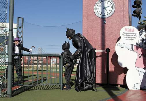 Batman and Batkid slowly sneak up on the Penguin who has kidnapped SF Giants' mascot Lou Seal at AT&T Park in San Francisco. Photo: Michael Macor, The Chronicle