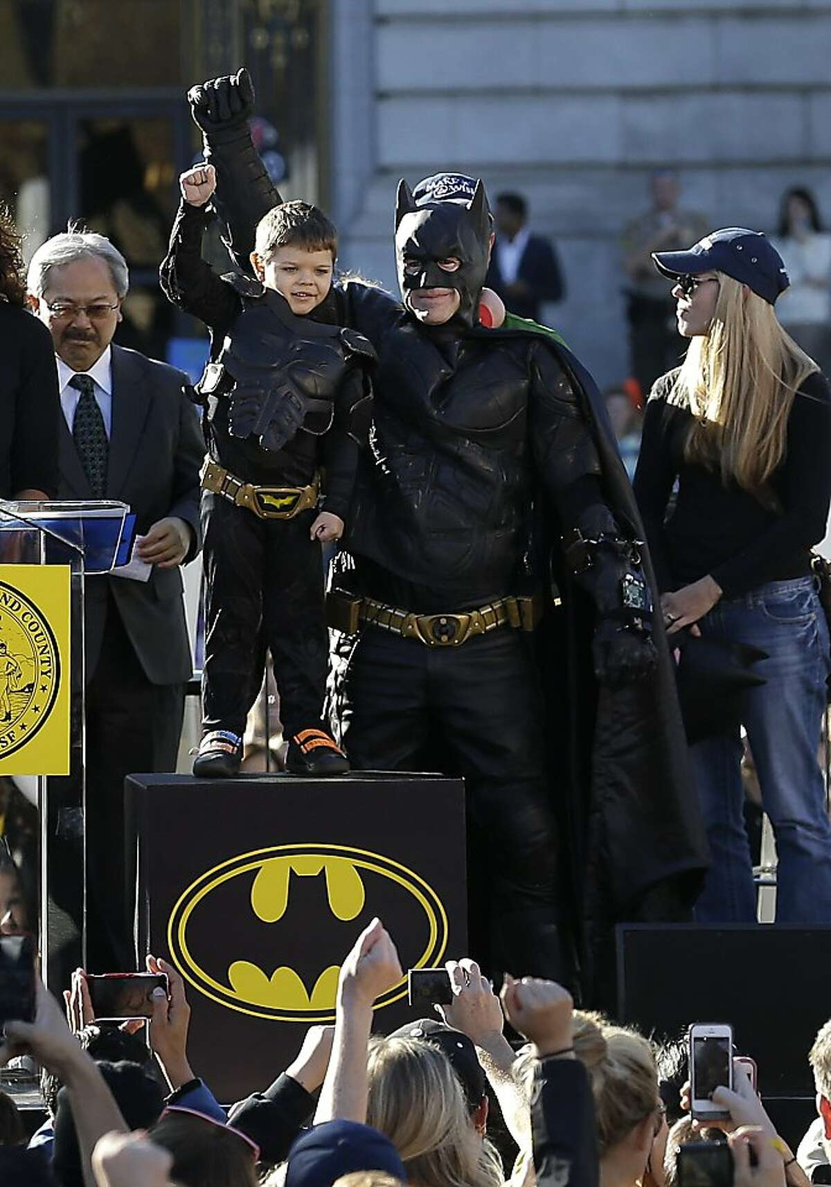 """Miles Scott, dressed as Batkid, second from left, raises his arm next to Batman at a rally outside of City Hall with Mayor Ed Lee, left, and his mother Natalie Scott in San Francisco, Friday, Nov. 15, 2013. Scott was called into service on Friday morning by San Francisco Police Chief Greg Suhr to help fight crime, as San Francisco turned into Gotham City as city officials helped fulfill the 5-year-old leukemia patient's wish to be """"Batkid,"""" The Greater Bay Area Make-A-Wish Foundation says. He was diagnosed with leukemia when he was 18 months old, finished treatment in June and is now in remission, KGO-TV reported. (AP Photo/Jeff Chiu)"""