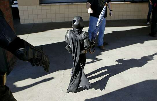 Batkid shows off the umbrella he recovered after a battle with the Penguin who kidnapped SF Giants' mascot Lou Seal and then was rescued by Batman and Batkid, at AT&T Park in San Francisco. Photo: Michael Macor, The Chronicle