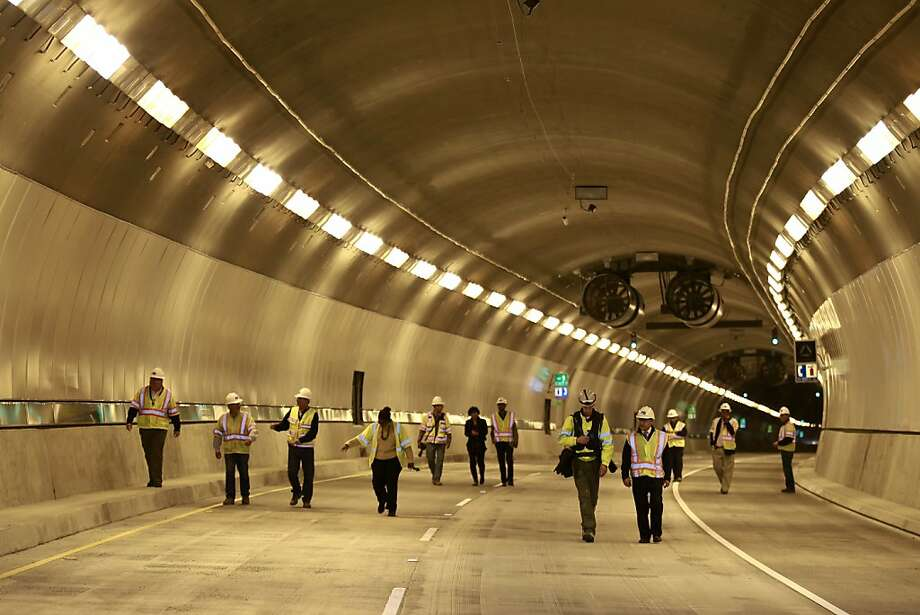 Transportation officials and members of the media emerge from the wider, taller and brighter fourth bore of the Caldecott Tunnel after being given a tour of the huge construction project. Photo: Beck Diefenbach, Special To The Chronicle