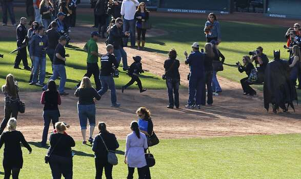 Batkid runs the bases after a battle the Penguin who kidnapped SF Giants' mascot Lou Seal at AT&T Park in San Francisco Ca., on Friday Nov. 15, 2013.  Five year old Miles from Tulelake in Siskiyou County loves superheroes and Batman in particular. After battling leukemia since he was a year old Miles will fulfill his dream of becoming Batkid being swept around the city performing superhero feats from rescuing a damsel in distress to thwarting a bank robbery and even chasing down the Penguin through AT&T Park Photo: Michael Macor, The Chronicle