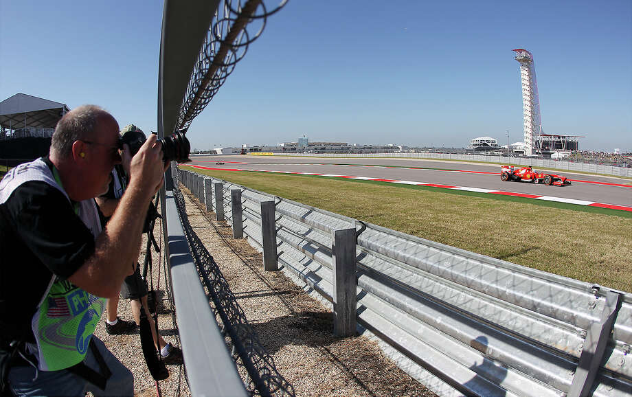 Scuderia Ferrari's Fernando Alonso zips past photographers during the Formula One United States Grand Prix morning practice session at the Circuit of the Americas near Austin, Texas on Friday, Nov. 15, 2013. Photo: Kin Man Hui, San Antonio Express-News / ©2013 San Antonio Express-News