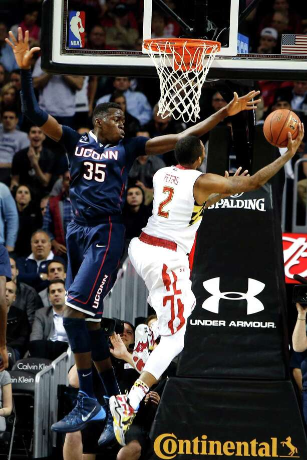 Connecticut's Amida Brimah (35) defends a shot from Maryland's Roddy Peters (2) during the first half of an NCAA college basketball game Friday, Nov. 8, 2013, in New York. (AP Photo/Jason DeCrow) Photo: Jason DeCrow, Associated Press / Associated Press