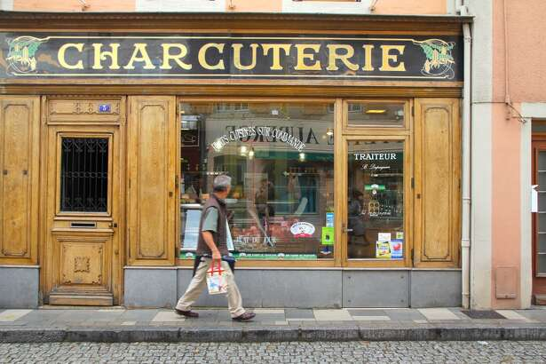 A man walks in front of a charcuterie in Cluny, France.