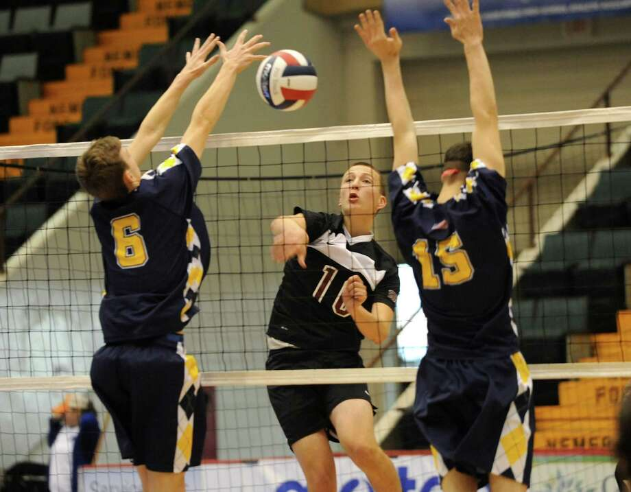 Dan Symer of Burnt Hills hits the ball past Matt Erickson, left, and Sean Harrington, right, of Sachem during a state semifinals volleyball match on Friday, Nov. 15, 2013 in Glens Falls, N.Y.  (Lori Van Buren / Times Union) Photo: Lori Van Buren / 00024609A