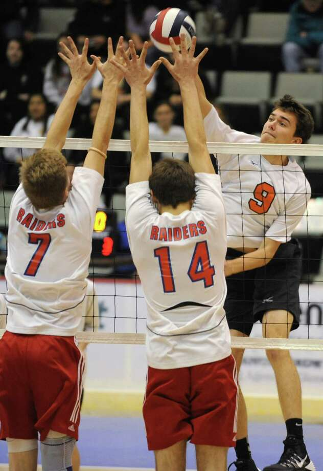 John Sica of Bethlehem hits the ball past Jamie Wolmering, left, and Josh Holm, right, of Fairport during a state semifinals volleyball match on Friday, Nov. 15, 2013 in Glens Falls, N.Y.  (Lori Van Buren / Times Union) Photo: Lori Van Buren / 00024609A