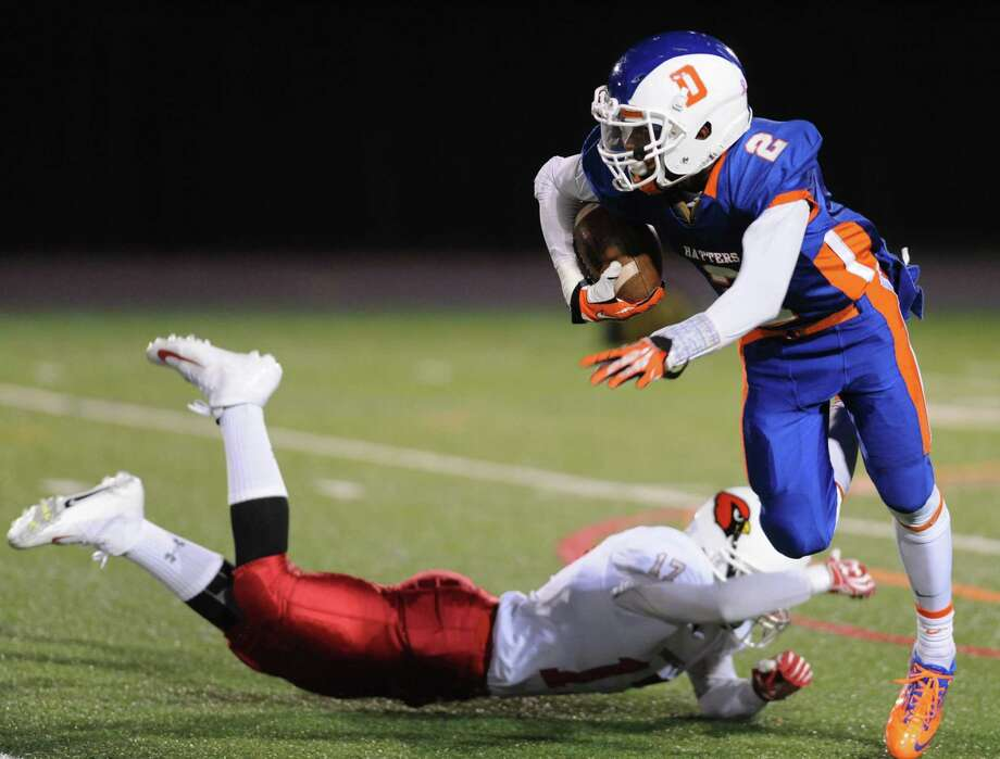 Danbury's Elijah Duffy (2) jukes Greenwich defender Jesse Prottas (17), returning a kick for a touchdown in the FCIAC high school football game between Danbury and Greenwich at Danbury High School in Danbury, Conn. on Friday, Nov. 15, 2013. Photo: Tyler Sizemore / The News-Times