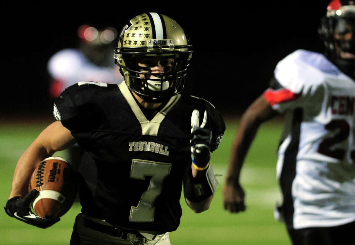 Trumbull's Thomas Hayduk carries the ball 70 plus yards for a touchdown, during football action against Central in Trumbull, Conn. on Friday November 15, 2013.