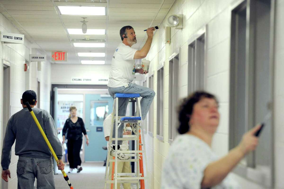 Jim Baker, center, and fellow National Grid employees work at painting walls of the East Greenbush YMCA on Friday Nov. 15, 2013 in East Greenbush, N.Y. National Grid encourages local employees to participate in community-based volunteer projects as a way to reach out and strengthen ties to the community. Projects are nominated by individuals with connections to the program and/or organization and help bring National Grid employees together from different departments for a day of team building, volunteering, cooperation and goodwill. (Michael P. Farrell/Times Union)