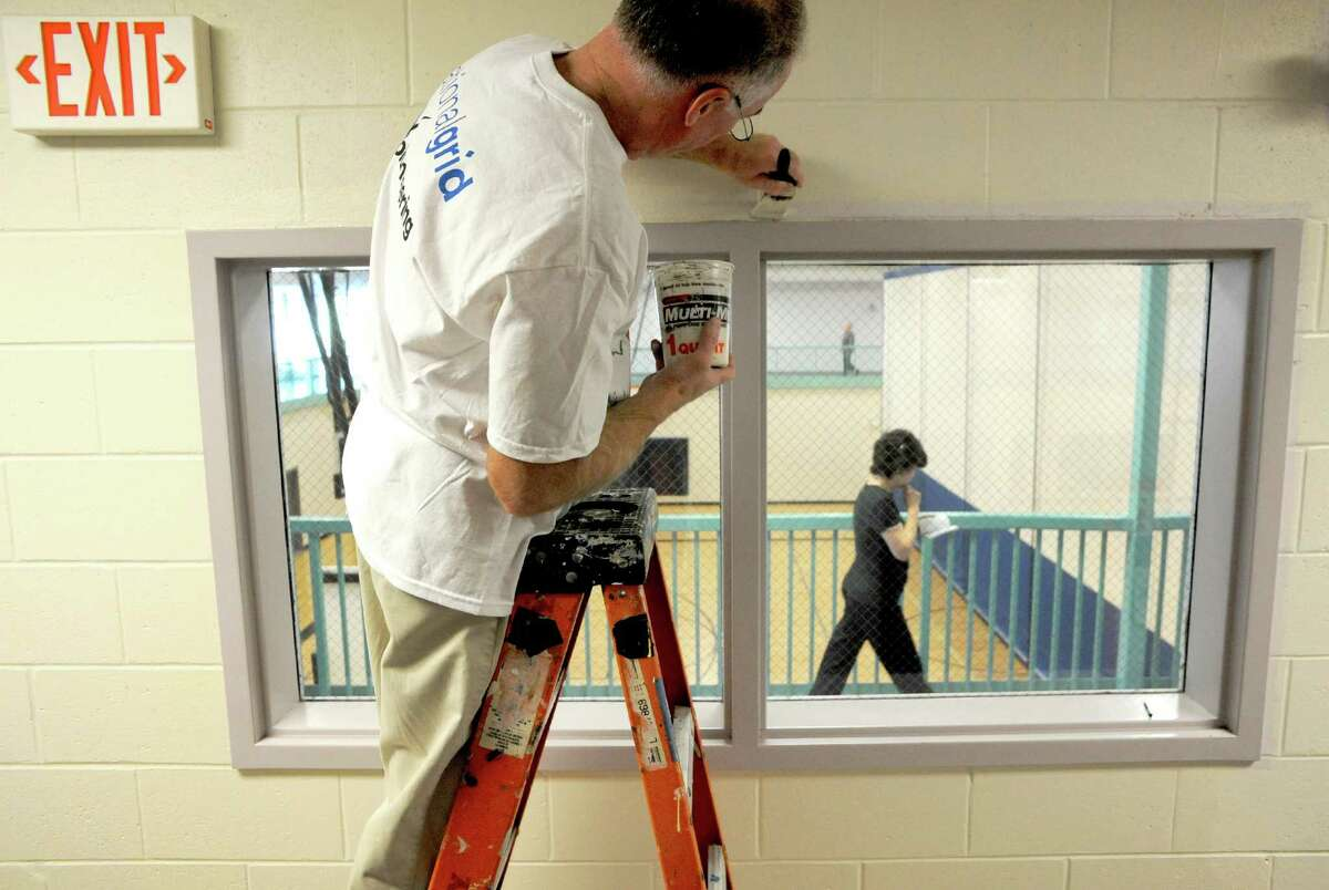 Kevin George of National Grid works at painting walls at the East Greenbush YMCA on Friday Nov. 15, 2013 in East Greenbush, N.Y. National Grid encourages local employees to participate in community-based volunteer projects as a way to reach out and strengthen ties to the community. Projects are nominated by individuals with connections to the program and/or organization and help bring National Grid employees together from different departments for a day of team building, volunteering, cooperation and goodwill. (Michael P. Farrell/Times Union)