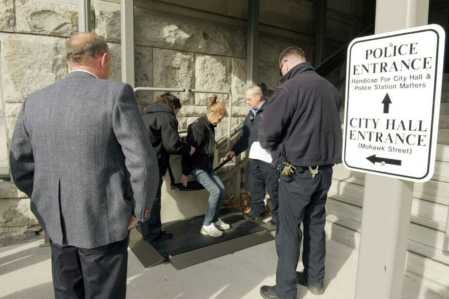 Mayor George Primeau , left, watches as a women uses the fully handicap accessible entrance, located on the Ontario Street side of City Hall, making City Hall and the Police offices accessible for all to do business on Friday Nov. 15, 2013 in Cohoes, N.Y.  (Michael P. Farrell/Times Union) Photo: Michael P. Farrell / 00024655A