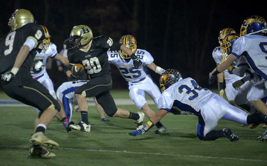 Barlow's Harry Wilson, 20, cuts through the Brookfield line as Gabe Pompette, 25, and Austin Reich, 34, try and stop him during a SWC football game between Brookfield and Joel Barlow High Schools. Played at Western Connecticut State University, Danbury, Conn, on Friday night, November 15, 2013. Photo: H John Voorhees III / The News-Times Freelance