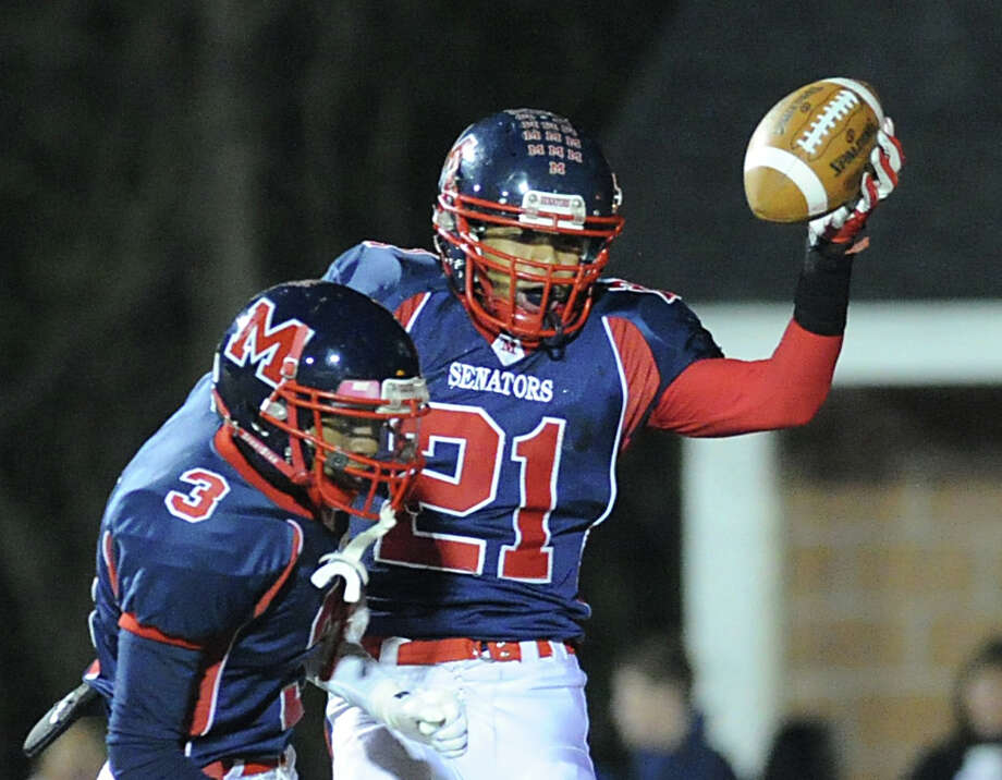 At right, Tim Hinton (# 21) of Brien McMahon celebrates his 2nd quarter running touchdown with teammate Javed Wright ( # 3) during the high school football game between Brien McMahon High School and St. Joseph High School at Brien McMahon in Norwalk, Friday night, Nov. 15, 2013. Photo: Bob Luckey / Greenwich Time