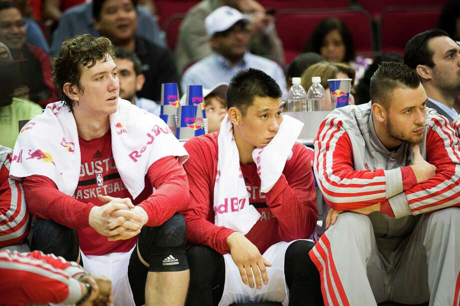 Omer Asik, left, does not like his new vantage point from which to watch the Rockets play. The center is joined on the bench by Jeremy Lin and Donatas Motiejunas. Photo: Smiley N. Pool, Staff / © 2013  Houston Chronicle
