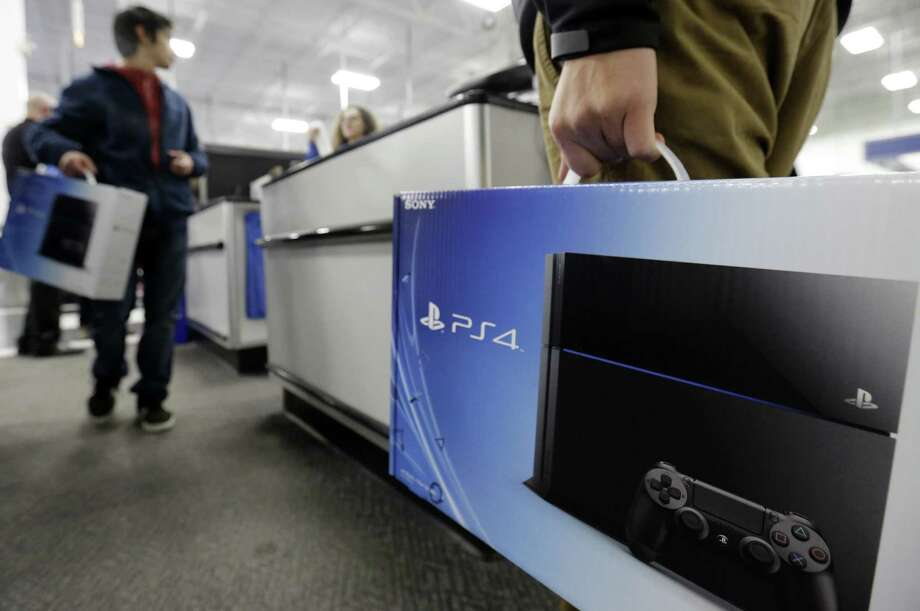 A man holds a Sony PlayStation 4 after he purchased it at the Lincoln Park Best Buy in Chicago. The PlayStation 4 came out Friday. The console video game maker's rival Microsoft is putting its Xbox One on sale next week. Photo: Nam Y. Huh / Associated Press