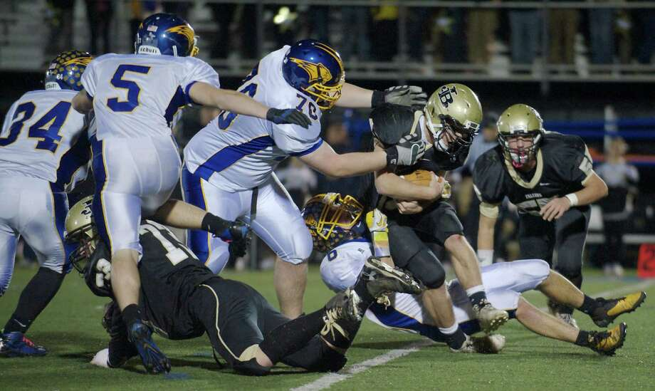Brookfield's Kyle Madden, 70, and Nick Seis, 6, tackle Barlow full back Stephen Miller, 33, during a SWC football game between Brookfield and Joel Barlow High Schools. Played at Western Connecticut State University, Danbury, Conn, on Friday night, November 15, 2013. Photo: H John Voorhees III / The News-Times Freelance