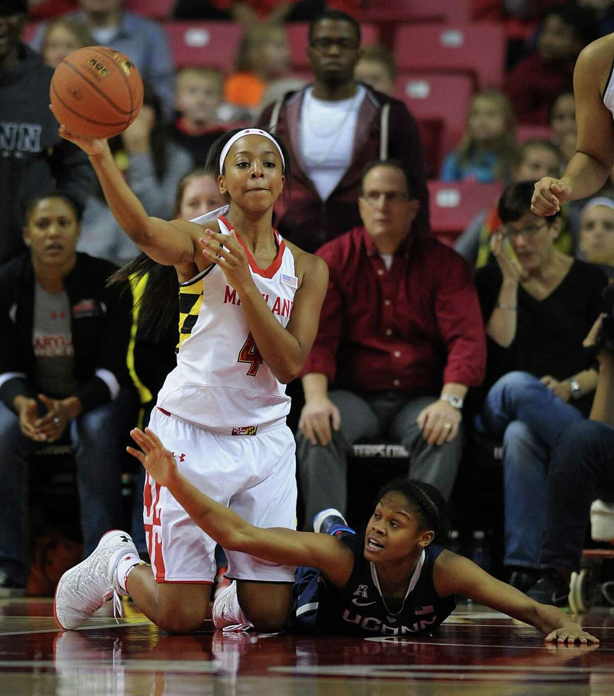 Maryland's Lexie Brown, left, passes from her knees as Connecticut's Moriah Jefferson struggles to block in the second half of an NCAA basketball game Friday, Nov. 15, 2013 in College Park, Md. Connecticut won 72-55.(AP Photo/Gail Burton)
