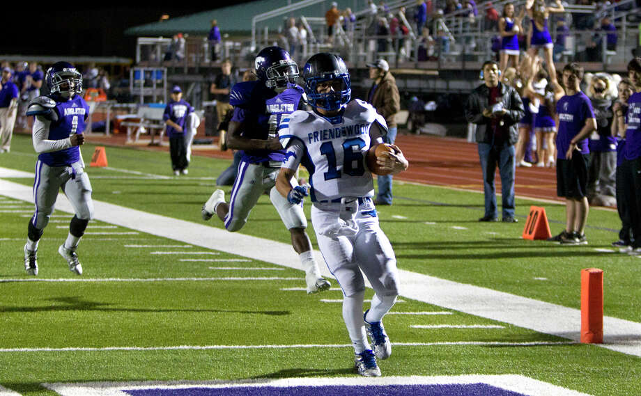 Friendswood High School wide receiver Tyler Page runs the ball in for a 57- yard touchdown as he's trailed by Angleton High School defenders during the first half of their matchup at Wildcat Stadium, Friday, Nov. 15, 2013, in Angleton. Photo: Cody Duty, Houston Chronicle / © 2013 Houston Chronicle