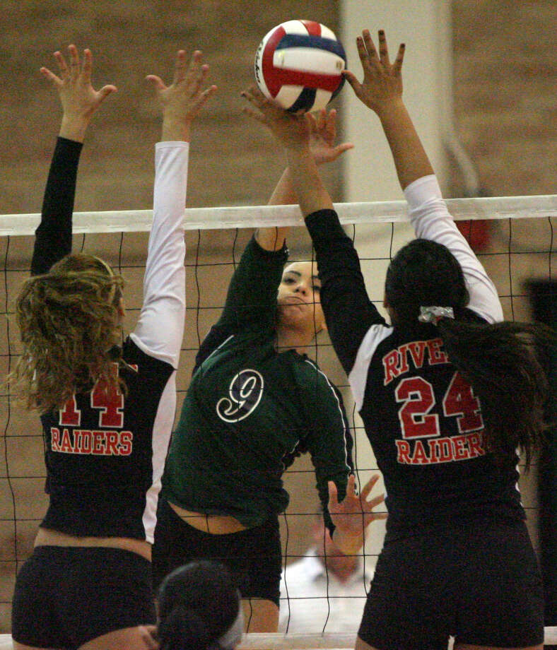 Reagan's Faith Squier (center) records one of the Rattlers' 41 kills during their regional semifinal victory over Brownsville Rivera. Photo: Delcia Lopez / For The Express-News