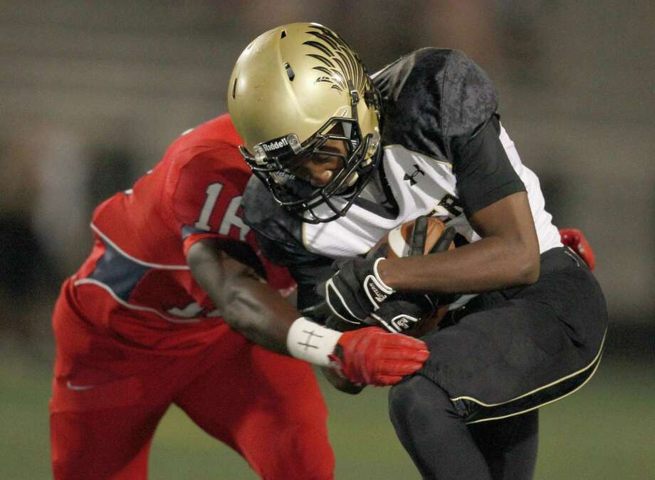 11/15/13: Foster Falcons  Brandon Taylor (11) is tackled by Dawson Eagles Travonte Moody (16) in a high school 4A  playoff football game at CCISD Veteran's Memorial Stadium in League City, TX. Photo: Thomas B. Shea, For The Chronicle / © 2013 Thomas B. Shea