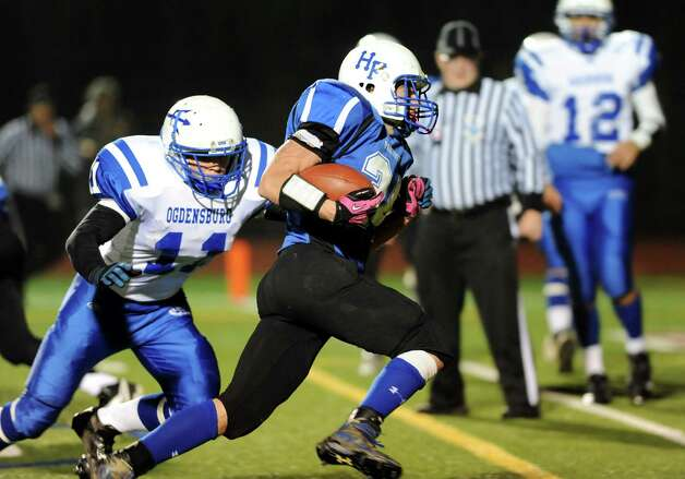 Hoosick Falls' Brandon Hodges, center, runs for a touchdown as Ogdenburg's Jordan McCormick defends during their Class C regional football semifinal on Friday, Nov. 15, 2013, at Stillwater High in Stillwater, N.Y. (Cindy Schultz / Times Union) Photo: Cindy Schultz / 00024622A