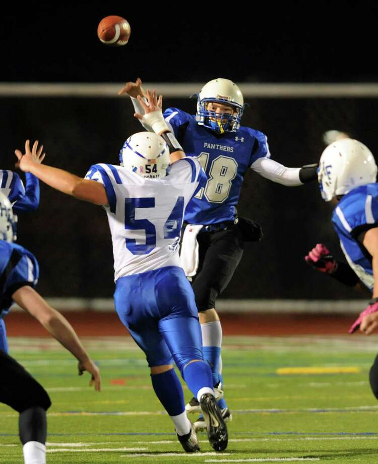 Hoosick Falls' quarterback Garrett Wright, center, releases a pass as Ogdensburg's Kevin Goolden defends during their Class C regional football semifinal on Friday, Nov. 15, 2013, at Stillwater High in Stillwater, N.Y. (Cindy Schultz / Times Union) Photo: Cindy Schultz / 00024622A