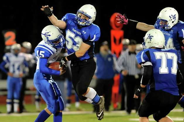 Hoosick Falls' Shayne Richard, center, pressures Ogdensburg quarterback Joe Dalton, left, during their Class C regional football semifinal on Friday, Nov. 15, 2013, at Stillwater High in Stillwater, N.Y. (Cindy Schultz / Times Union) Photo: Cindy Schultz / 00024622A