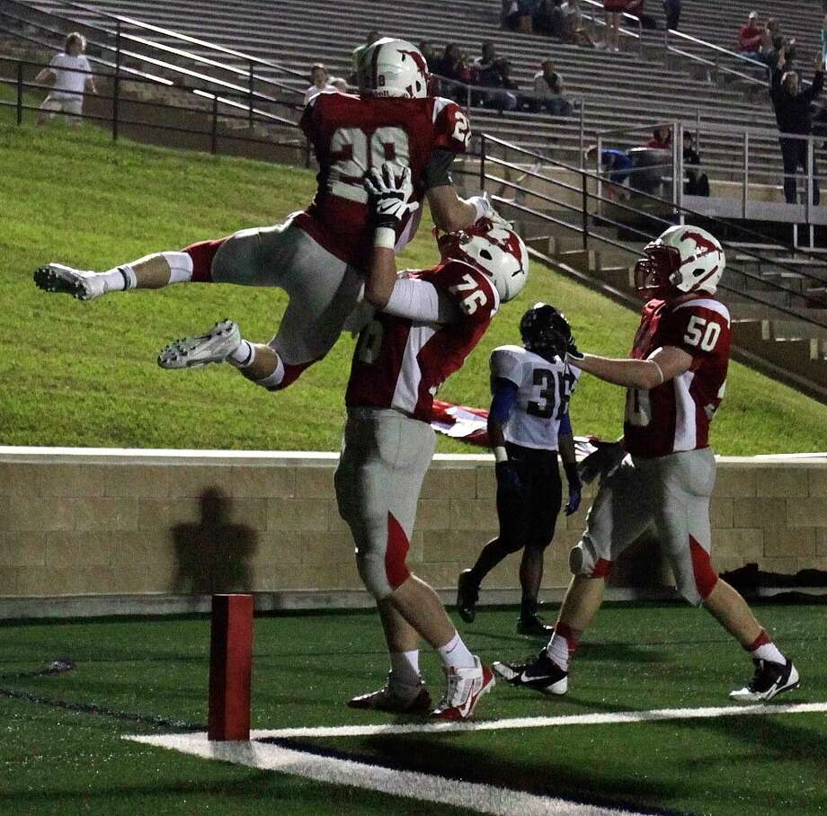 Memorial's Matt Collins (28) celebrates his 15-yard touchdown run with teammateMax McCauley (76) and Michael Moody (50) during the second half of a high school football bi-district playoff game against Westside, Friday, November 15, 2013, at Tully Stadium in Houston. Photo: Eric Christian Smith, For The Chronicle
