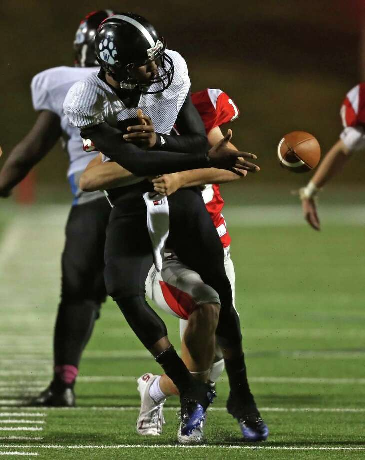 Westside's Michael Haywood passes the ball off after being tackled by Memorial's Austin Nichols during the second half of a high school football bi-district playoff game, Friday, November 15, 2013, at Tully Stadium in Houston. Photo: Eric Christian Smith, For The Chronicle