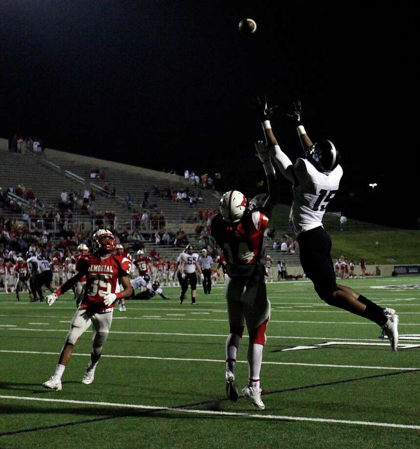 Westside's Frankj Iheanacho, right, hauls in a 20-yard touchdown reception over Memorial's Harrison Sladic (14) as teammate Andrew Giammalva looks on during the first half of a high school football bi-district playoff game, Friday, November 15, 2013, at Tully Stadium in Houston. Photo: Eric Christian Smith, For The Chronicle