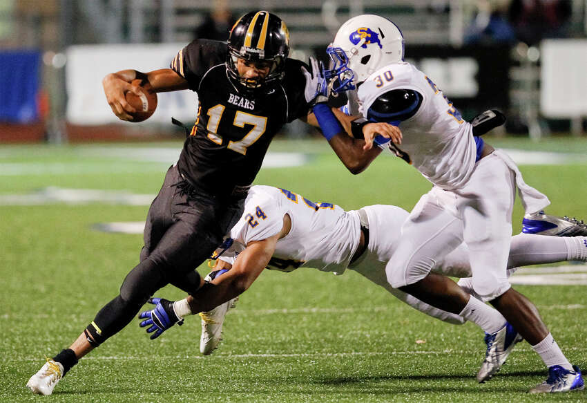 Brennan's Da'Shawn Key (left) tries to run past Clemens' Jeremy Dickey (right) and Norman Reeves during the first half of their Class 4A Division I first round playoff game at Farris Stadium on Friday, Nov. 15, 2013. MARVIN PFEIFFER/ mpfeiffer@express-news.net