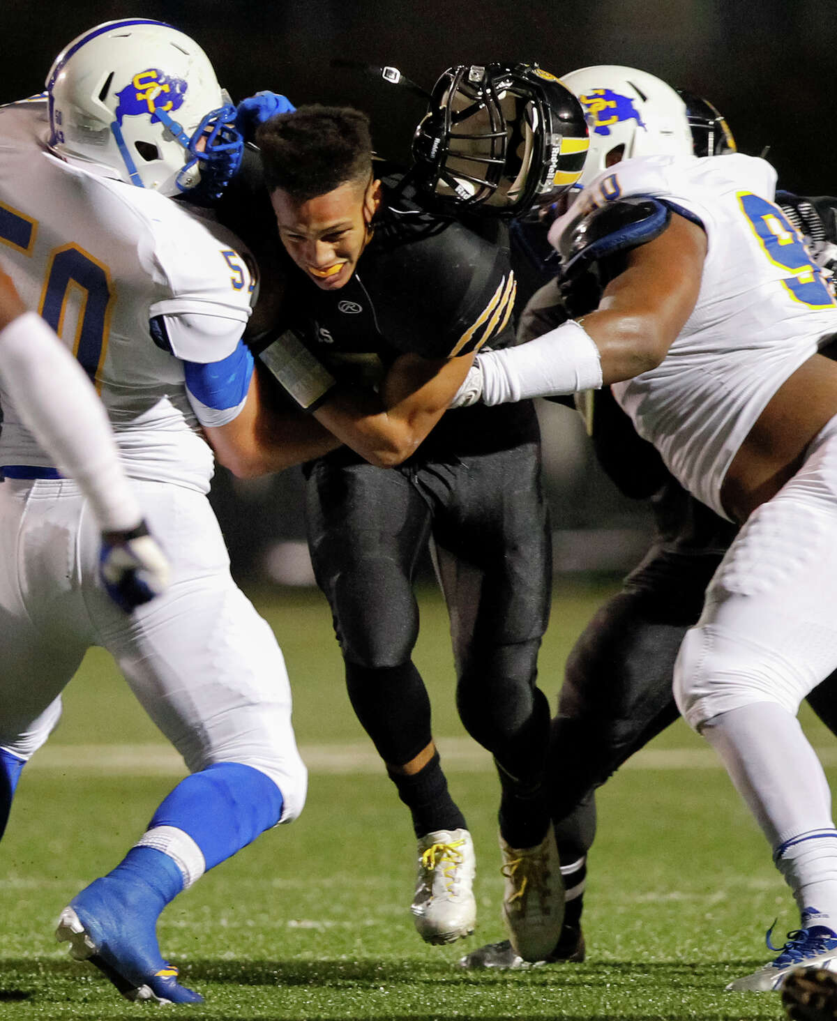 Da'shawn Key (center) loses his helmet as he runs between Clemens Tristen Blake (left) and Eugene Sutton during the first half of their Class 4A Division I first round playoff game at Farris Stadium on Friday, Nov. 15, 2013. MARVIN PFEIFFER/ mpfeiffer@express-news.net