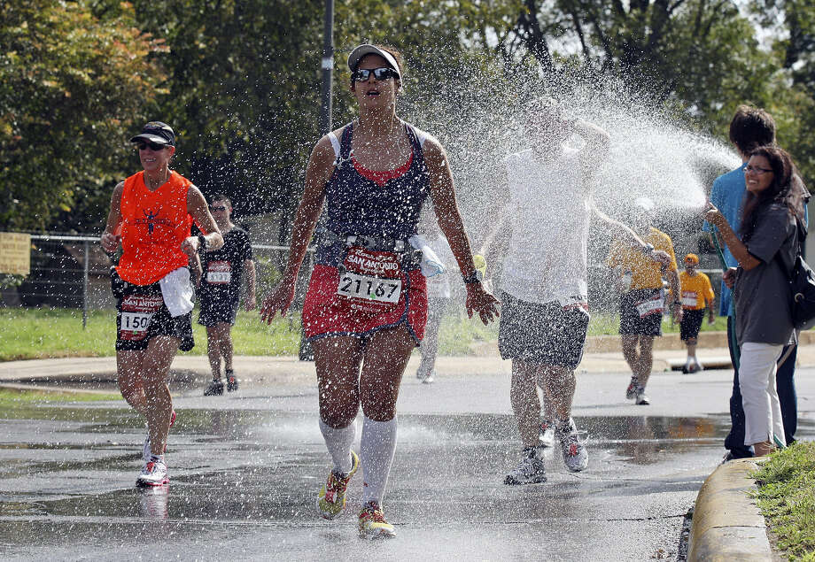 Runners were sprayed with water during last year's marathon, when temperatures reached into the 80s by midday. Photo: San Antonio Express-News File Photo