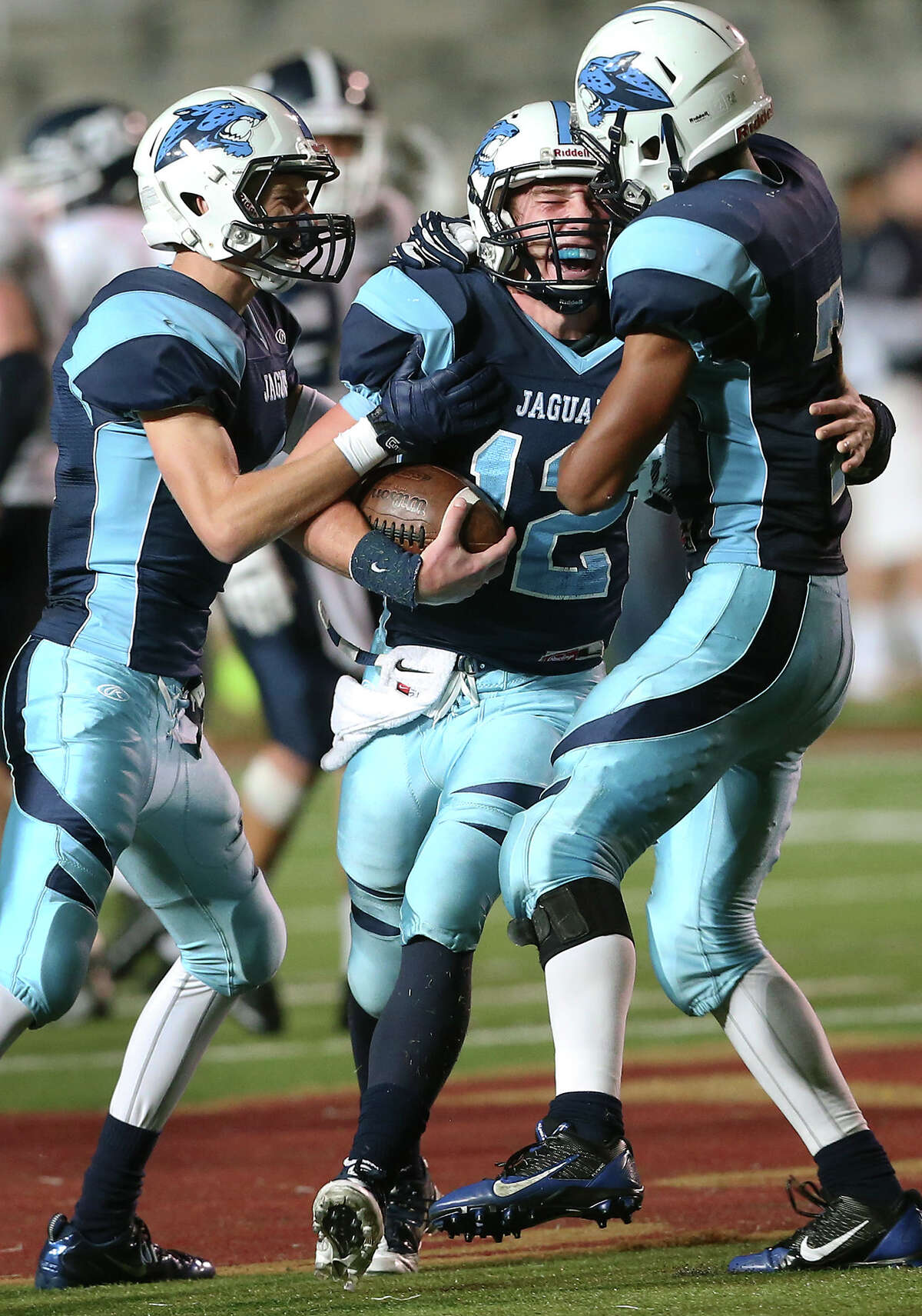 Jaguar quarterback Hunter Rittimann celebrates with the game ball as teammates Coleman Fowler (left) and Darion McElhannon converge as Johnson beats Smithson Valley 49-45 in the first round of football playoffs at Bobcat Stadium in San Marcos on November 15, 2013.
