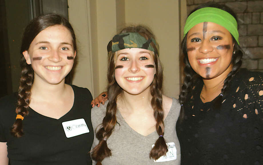 "Running the military obstacle course at Westport Library's ""Hunger Games"" event Friday evening were Westporters Clemmy Fowle, 15; Rebecca Zlatkin, 16, and Laura Londono, 16. Photo: Mike Lauterborn / Westport News contributed"