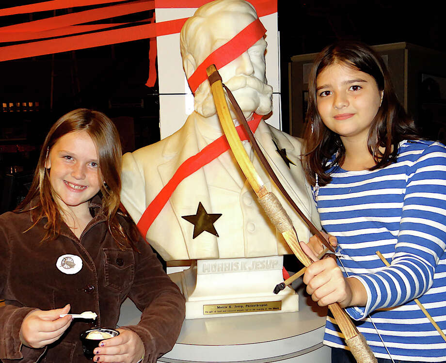 "Westport freinds Emily McNee, 10, and Fillipa Ramos, 11, enjoy the Westport Library's ""Hunger Games"" event Friday evening. Photo: Mike Lauterborn / Westport News contributed"