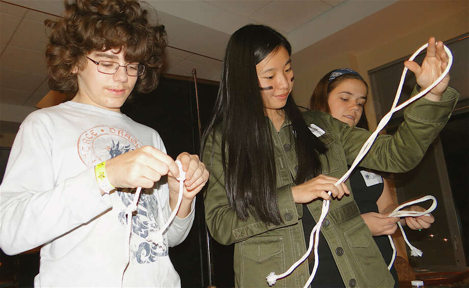 "Joey LoRusso, 13; Claudia Chen, 15, and Caroline Lane, 15, try knot-tying at the ""Hunger Games"" on Friday at the Westport Library. Photo: Mike Lauterborn / Westport News contributed"