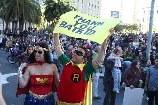 Heather Avakian, dressed as Wonder Woman, and Jesse Buman, dressed as Robin, hold a sign thanking Batkid in Union Square during a Make-a-Wish benefit where Miles Scott, 5 saves Gotham as Batkid in San Francisco, Calif., Friday November 16, 2013. Photo: Jason Henry, Special To The Chronicle
