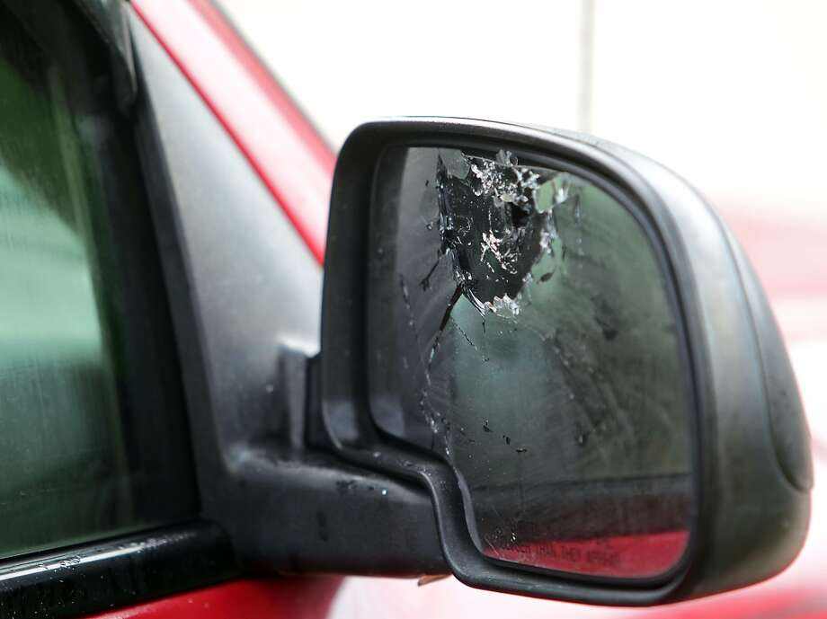 A bullet hole in the mirror of a vehicle at the scene of a shooting outside a party in the 4400 block of Tiffany Saturday, Nov. 16, 2013, in Houston.  ( James Nielsen / Houston Chronicle ) Photo: James Nielsen, Houston Chronicle