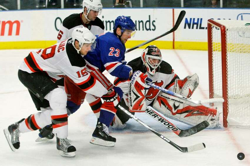 New Jersey Devils' Travis Zajac (19) and New Jersey Devils goalie Martin Brodeur defend New York Rangers' Chris Drury (23) during the second period of an NHL hockey game Thursday, Oct. 22, 2009, in New York. (AP Photo/Frank Franklin II)